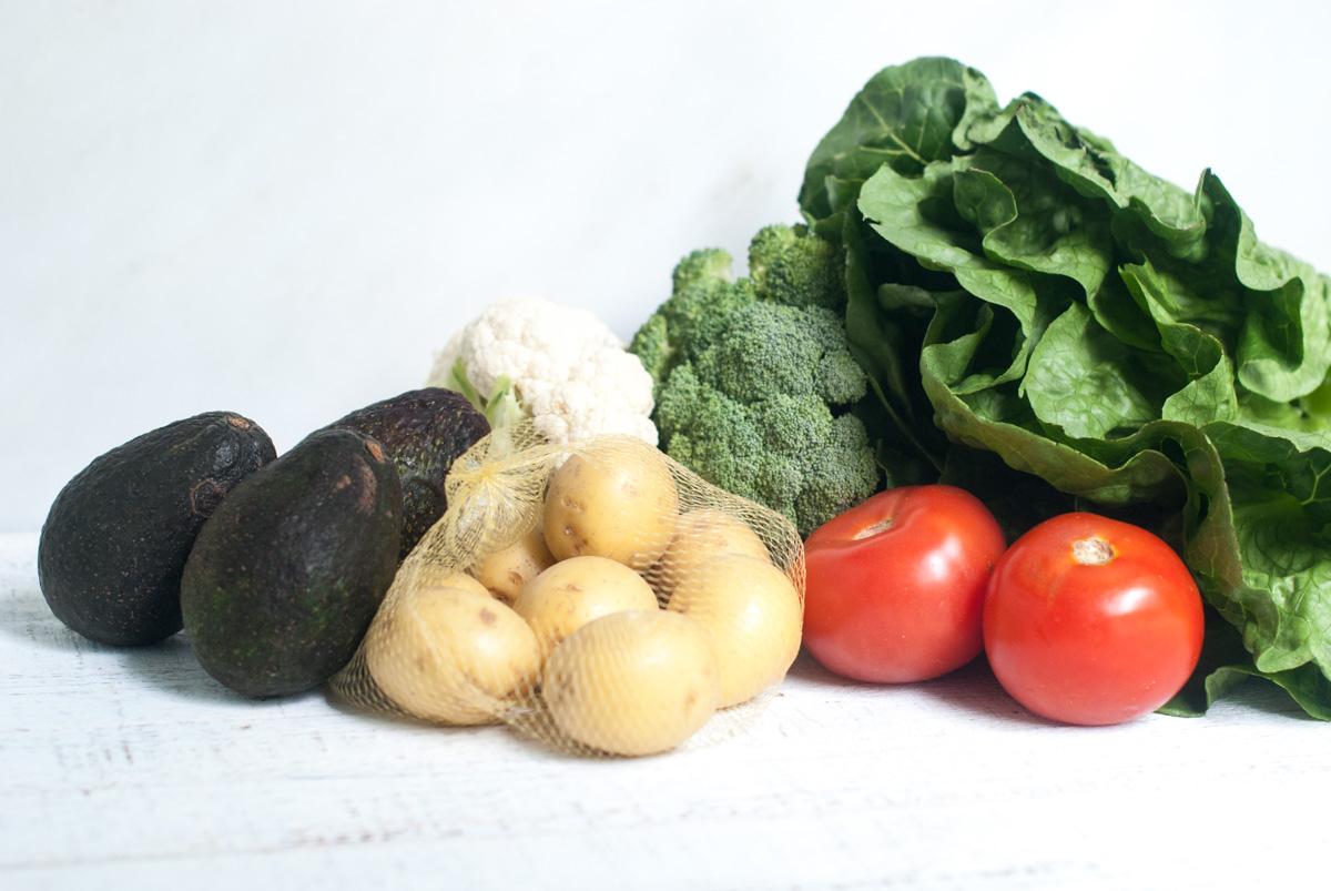 An assortment of fresh produce including tomatoes, cauliflower, avocado, potatoes, broccoli and Romaine lettuce.