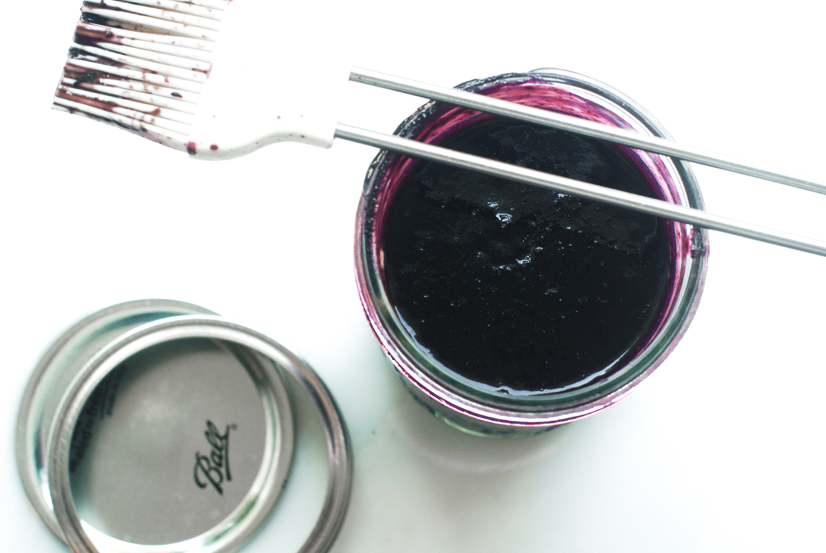 A mason jar of blueberry bbq sauce with a pastry brush for basting.