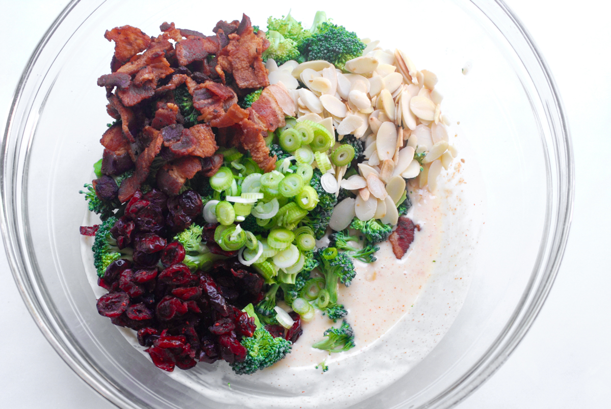 A big mixing bowl with bacon, dried cranberries, green onion, almonds, broccoli and seasoned mayo ready to be combined all together.