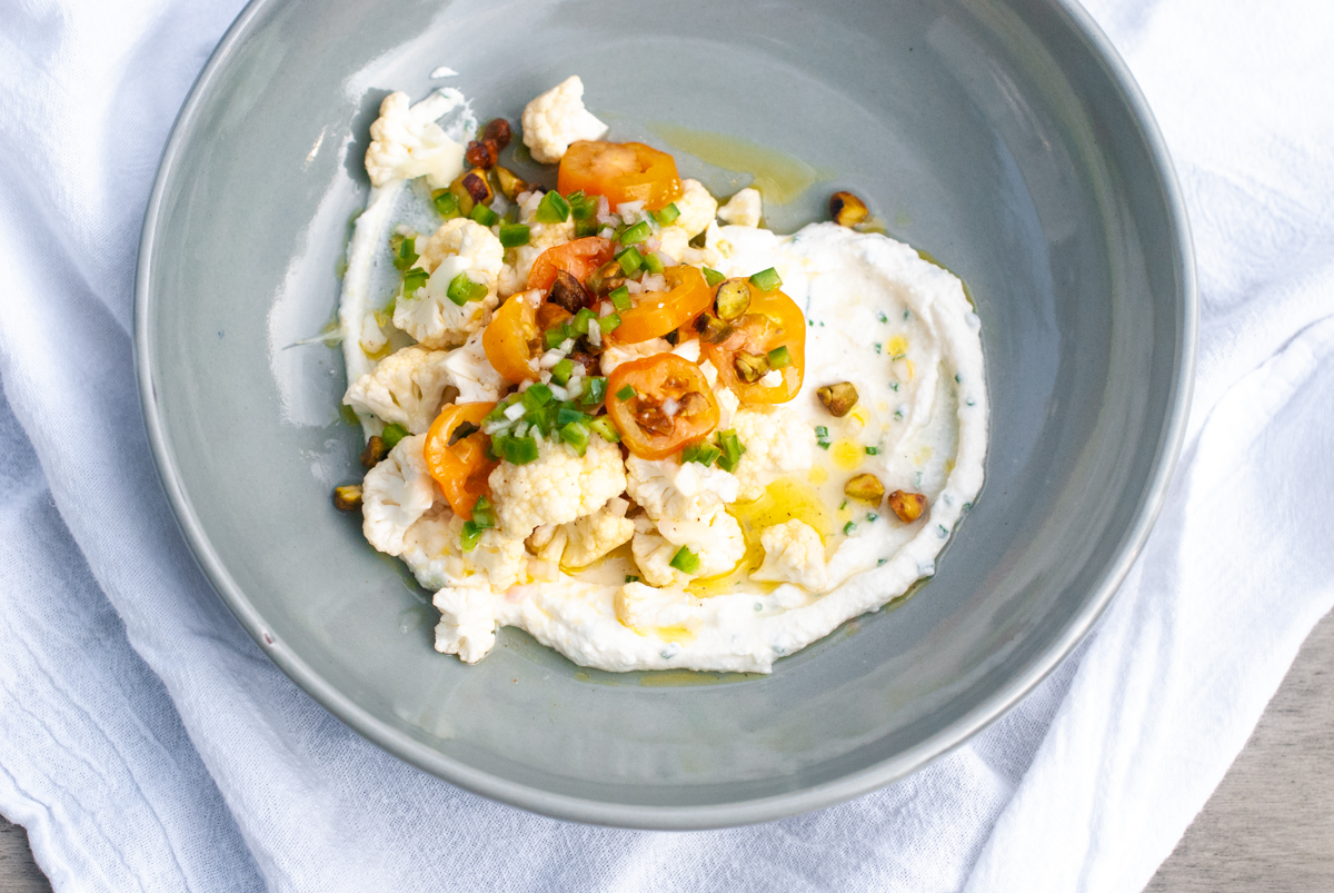 A grey bowl with a swoop of chive ricotta and topped with a salad of raw cauliflower florets and sliced cherry tomatoes