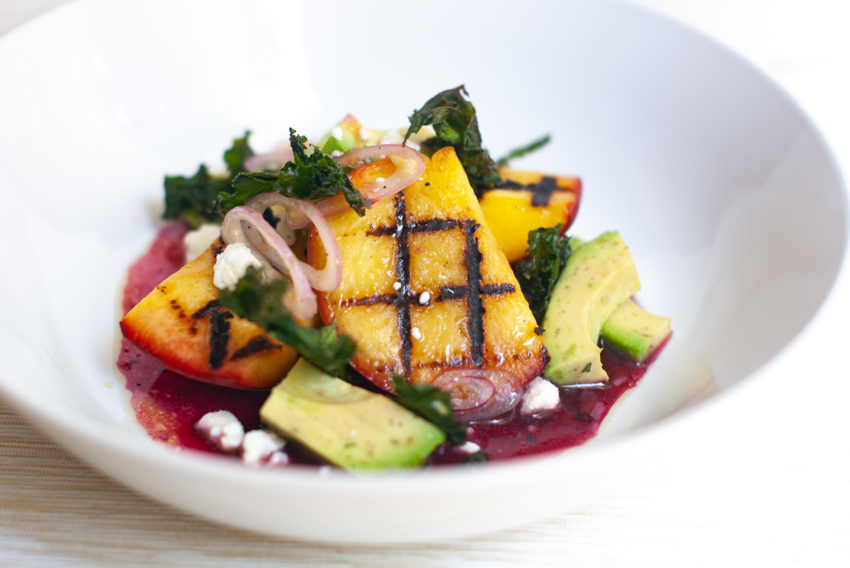 Bowl of grilled peaches in a salad of avocado, feta, crispy kale and a blueberry vinaigrette.
