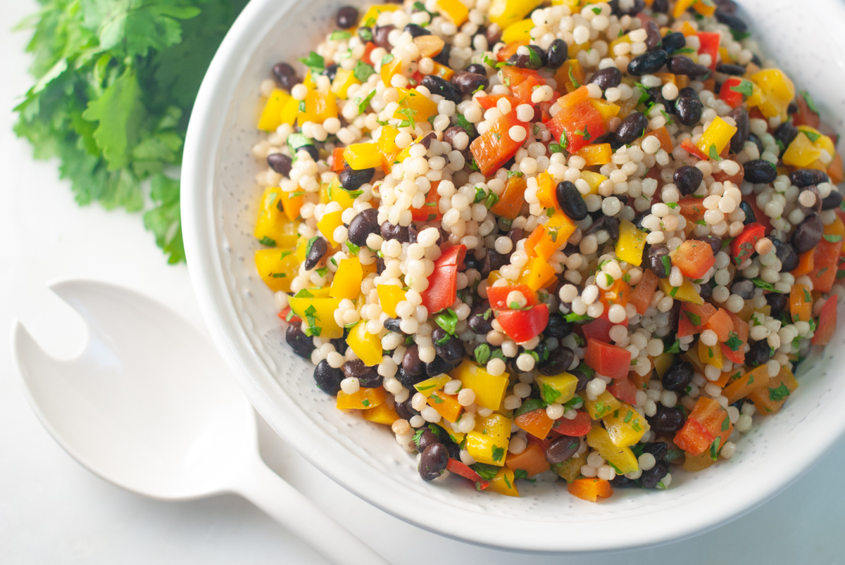 A bowl of pearl couscous tossed with red, yellow and orange diced bell peppers, black beans and chopped cilantro.