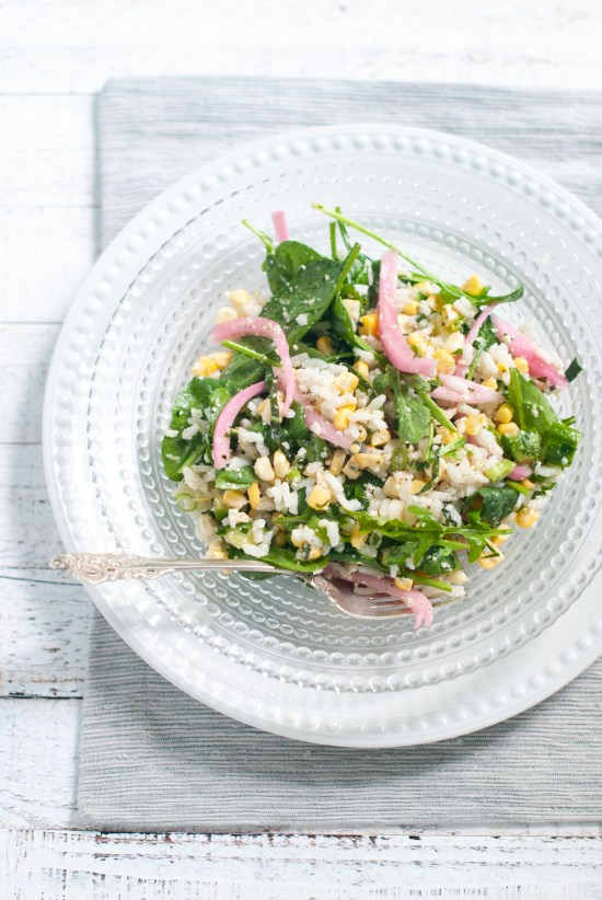 A bowl of risotto rice with corn, cucumber, avocado, baby spinach and pickled red onions.