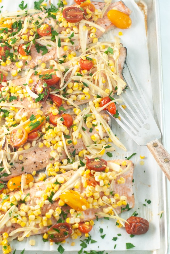 Trout filets topped with sliced fennel, cherry tomatoes and corn kernels after being baked in the oven.