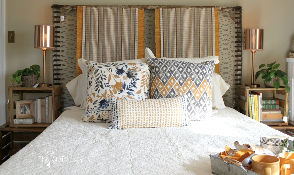 Master Bedroom with tons of DIY inspiration. A headboard made from a vintage bedspring embellished with decorative rugs. Nightstands made from stacked crates.