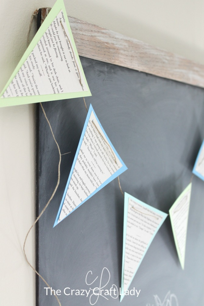 DIY Spring Banner - Follow this tutorial to make a book page pennant banner using pages from an old book and scrapbook paper. This is the perfect upcycle craft for spring!