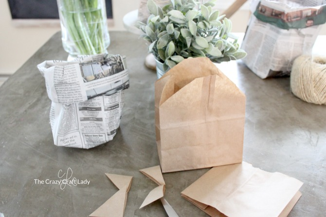 Make a fun and stylish newspaper bag planter for a house plant or spring greenery with a sheet of newspaper with this easy upcycle craft tutorial.