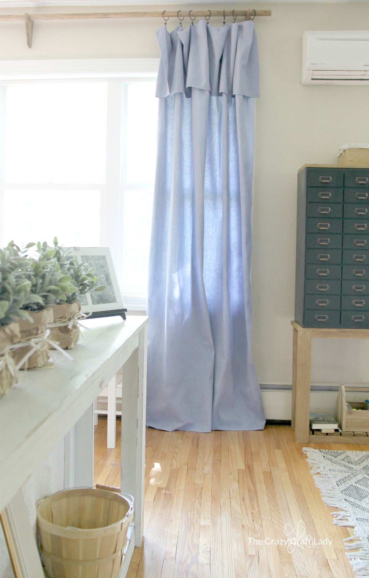 Save TONS of money on drapery with these DIY no-sew drop cloth curtains. Make easy and inexpensive curtains and a DIY curtain rod on a tiny budget. Farmhouse style curtains and wood farmhouse drapery rod.