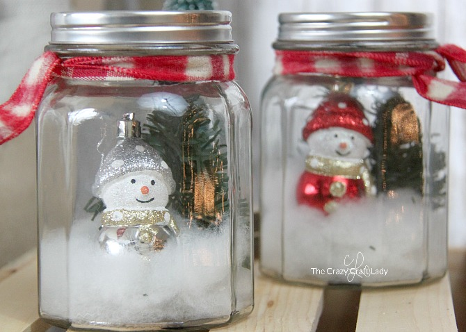 Use dollar store supplies to make a snowy winter scene in a DIY mason jar snow globe. Follow this simple tutorial and learn how to make a dollar store snow globe jar. Perfect winter craft - Christmas decor project.