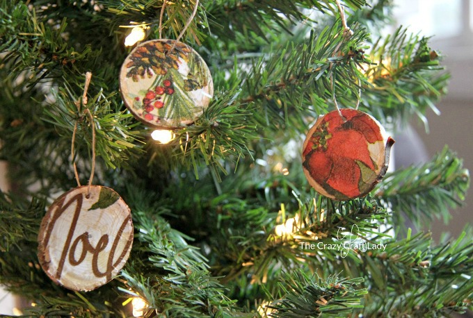 How to make DIY decoupage ornaments on wood round slices. This is an easy way to your own tree ornaments. Use a paper napkin or tissue paper in any pattern or color to make custom ornaments that match your Christmas decorating style.