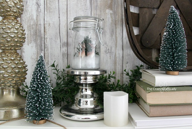 How to make a mini snow globe in a glass jar. This simple winter craft will make a beautiful addition to your winter decor. How to make a DIY glass jar snow globe.