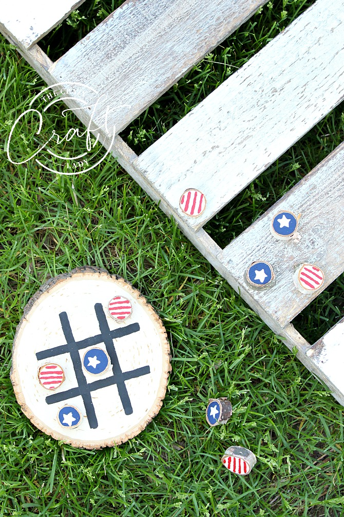 Painted stars and stripes wood round tic-tac-toe game on grass