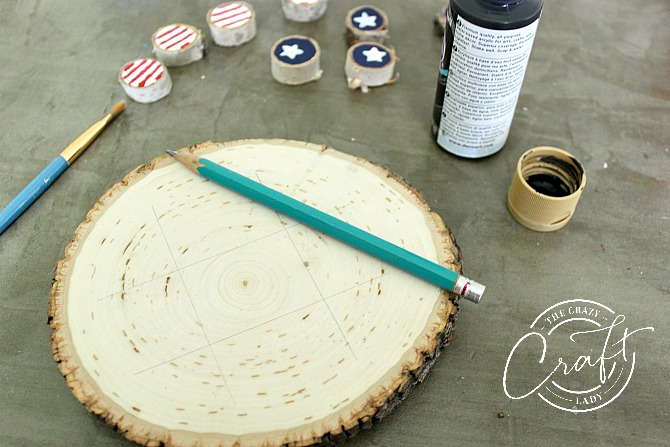 painting a tic-tac-toe board on a large wood round