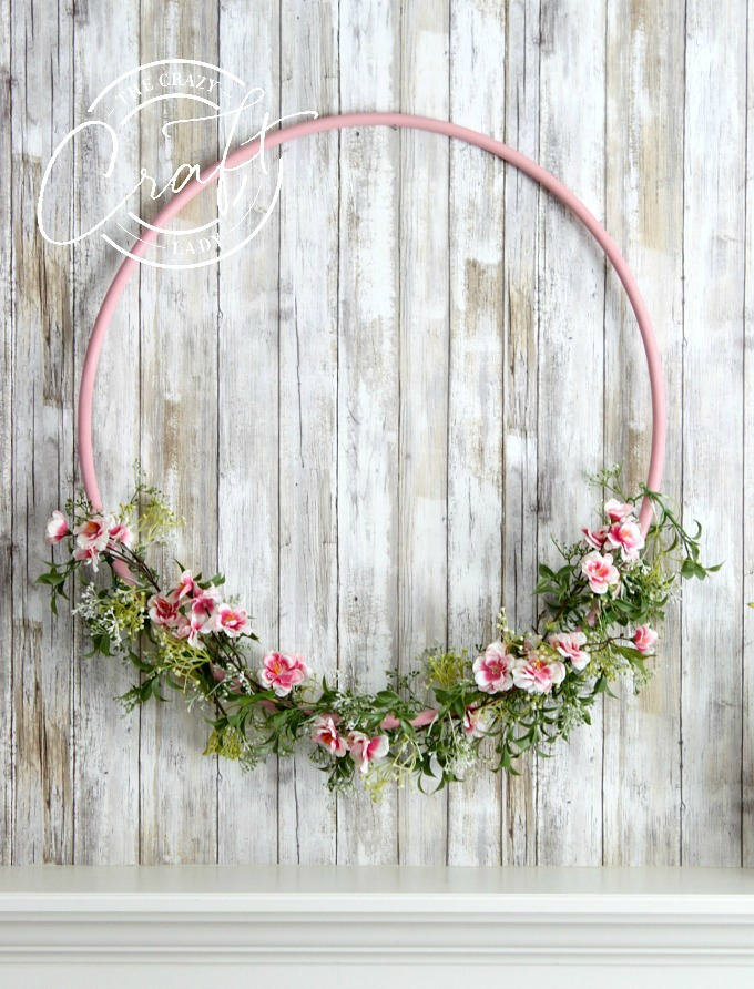I made this sweet spring hula hoop wreath with a few simple supplies. Make this large wreath in any color and type of flower you like. This cherry blossom wreath will make a cheery addition to your spring decor.