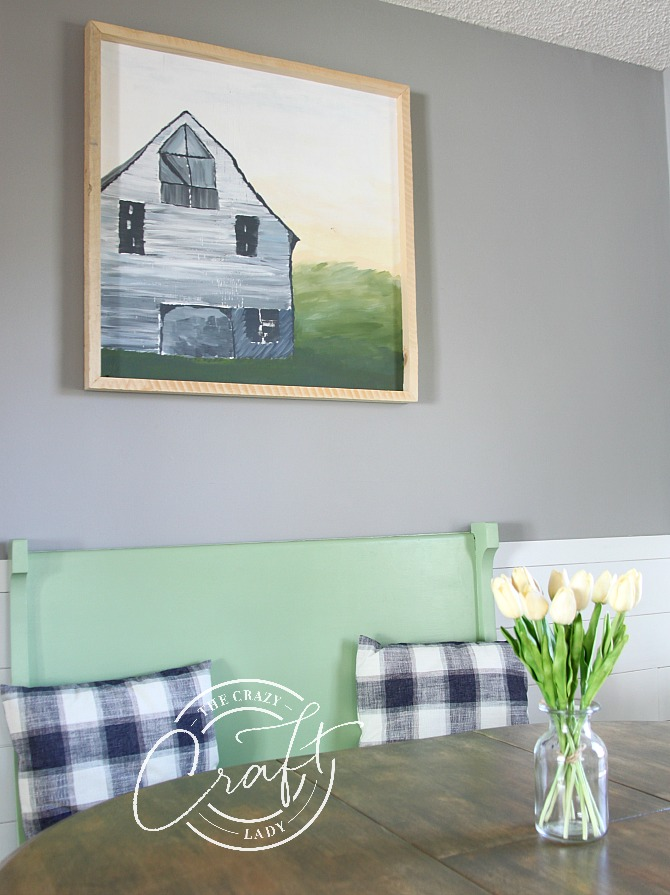 a barn painting hung above a green dining room bench
