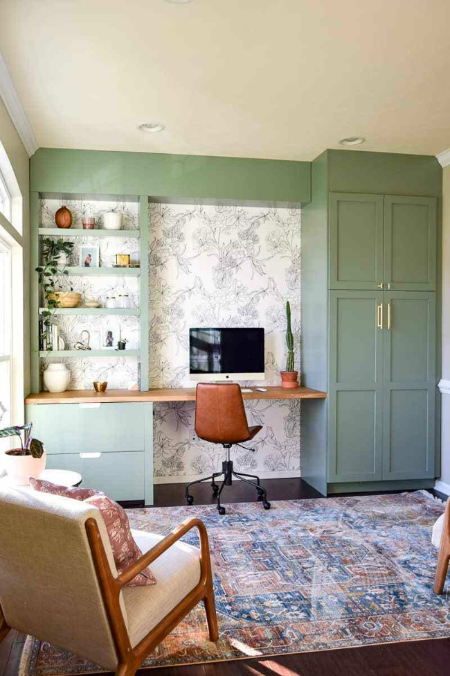 Home office with green painted ikea built in cabinets and shelves