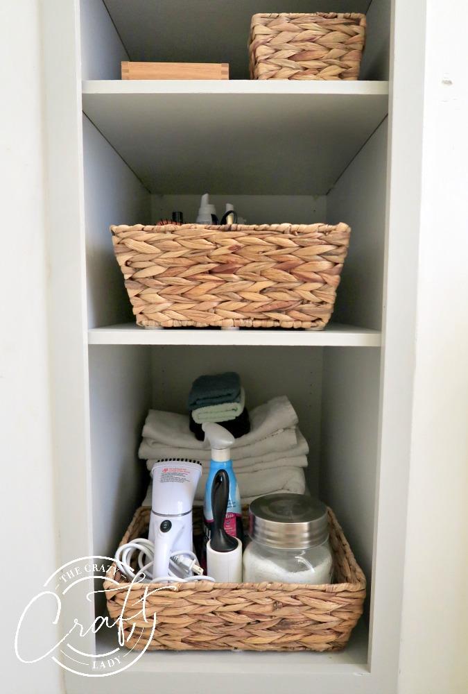 baskets and spare towels on a bathroom shelf