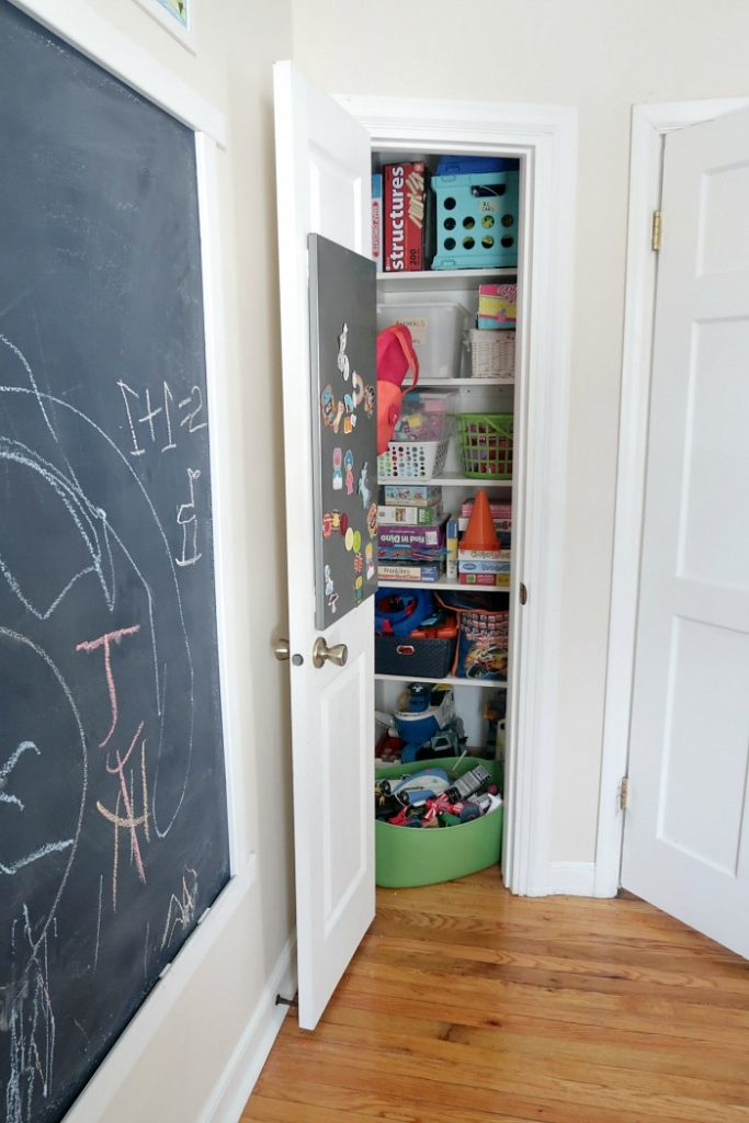 kids playroom with a chalkboard wall and organized toy closet