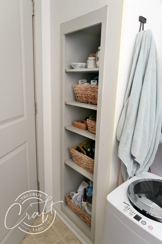 shelves and a portable washing machine in the bathroom