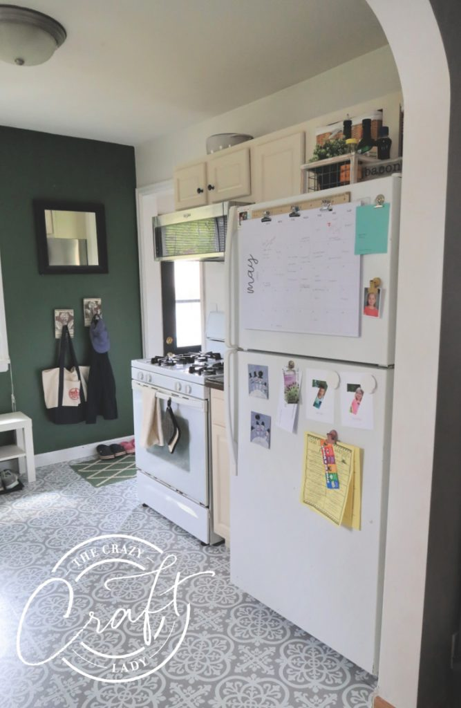 painted neutral kitchen cabinets and dark green accent wall