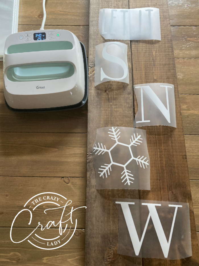 arranging vinyl letters onto a vertical winter porch sign