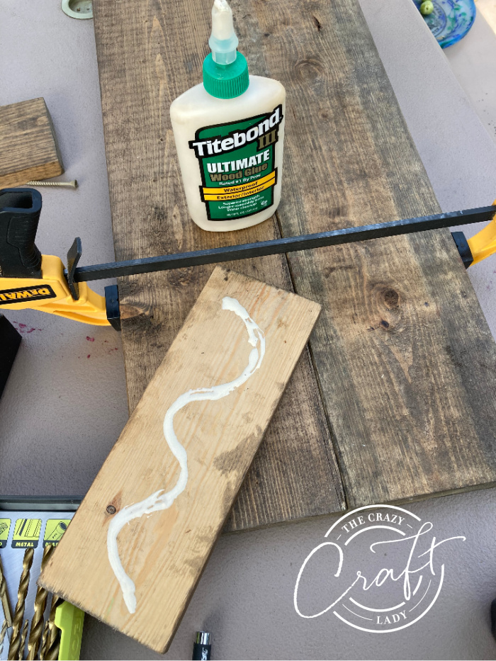gluing wood pieces to make a plank porch sign