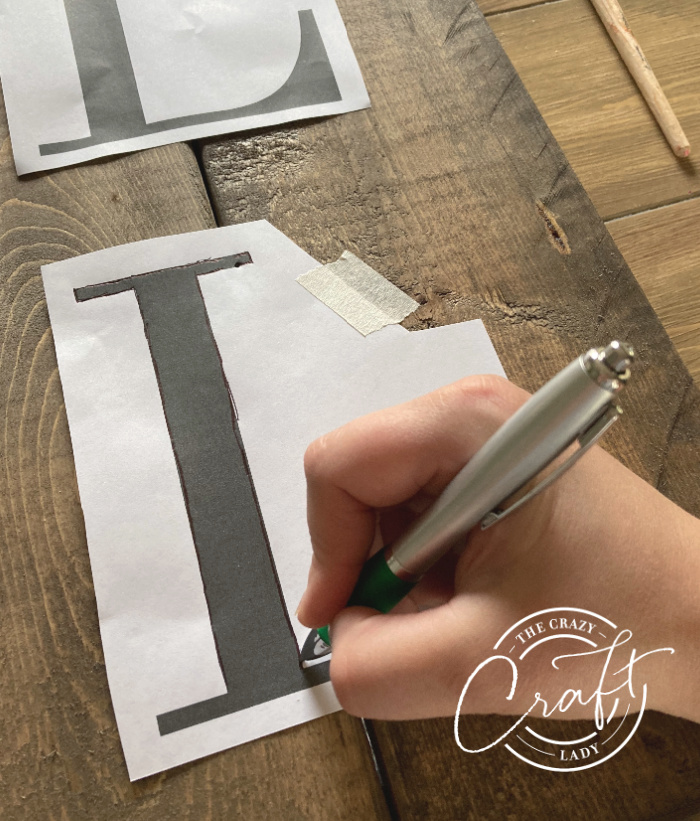 tracing letters onto a plank wood sign