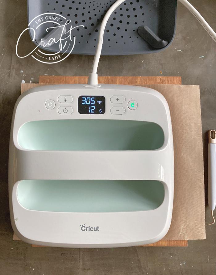 using a Cricut EasyPress to add heat transfer vinyl to wood