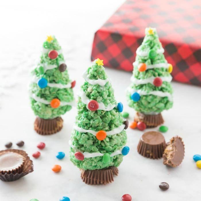Three Rice Krispie treats shaped into Christmas trees and decorated with candy baubles.