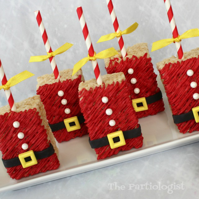 A group of Santa decorated Rice Krispie treats on a plate.