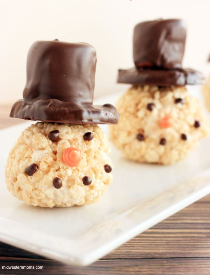 Two Rice Krispie treats decorated to look like snowmen, with chocolate hats.
