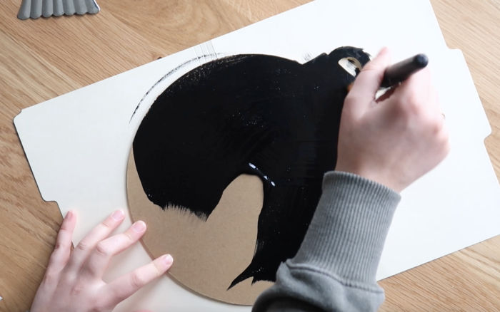 Use a large flat paint brush to cover the unfinished back and edges of the ornament hanger with black chalkboard paint