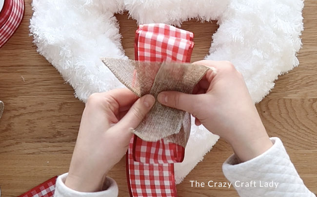 Stack the burlap ribbon on top of the red ribbon