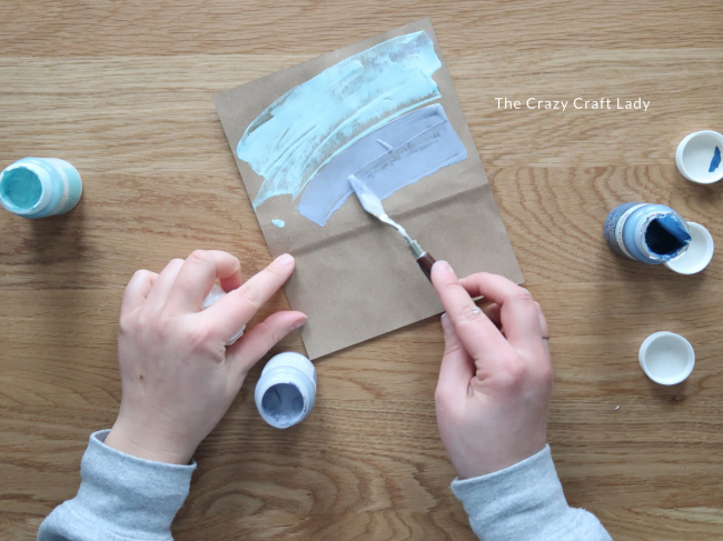 Use a palette knife to spread paint across the paper bag