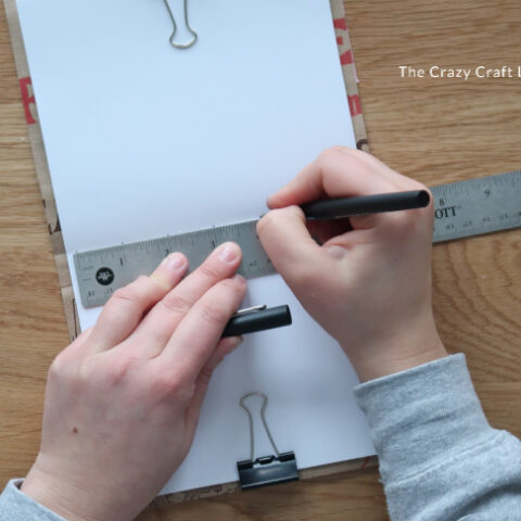 Use a ruler and marker to mark even intervals along the inside seam of the paper