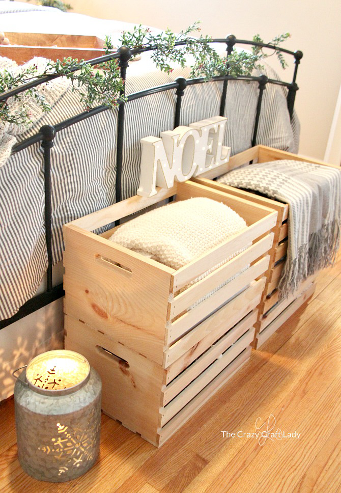 Wooden crates filled with blankets at the end of a bed.
