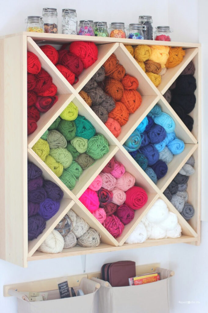 Colorful yarn stored in wooden wine rack.
