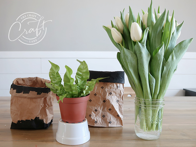 arranging fresh flowers and plants in paper bag vases