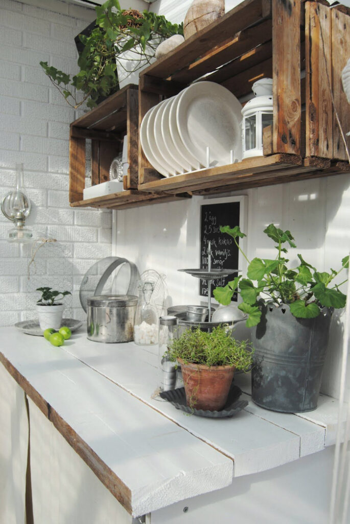 Wooden crates used as top cabinets in an outdoor kitchen.