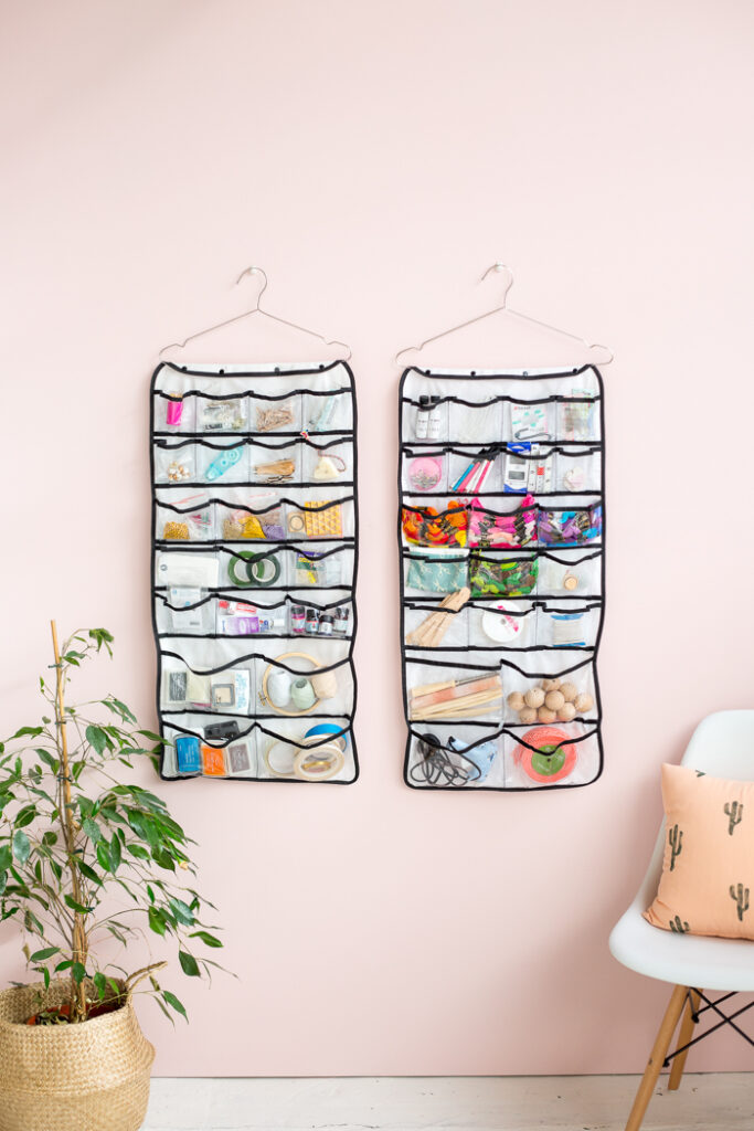 Clear storage pockets hanging on a wall and filled with craft supplies