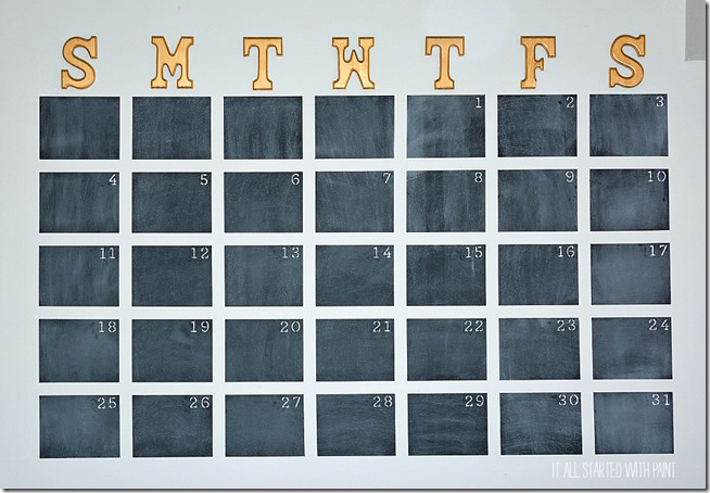 A chalkboard calendar with spaces for each day of the month.