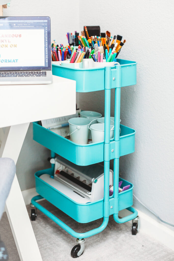 A teal storage cart next to a desk.