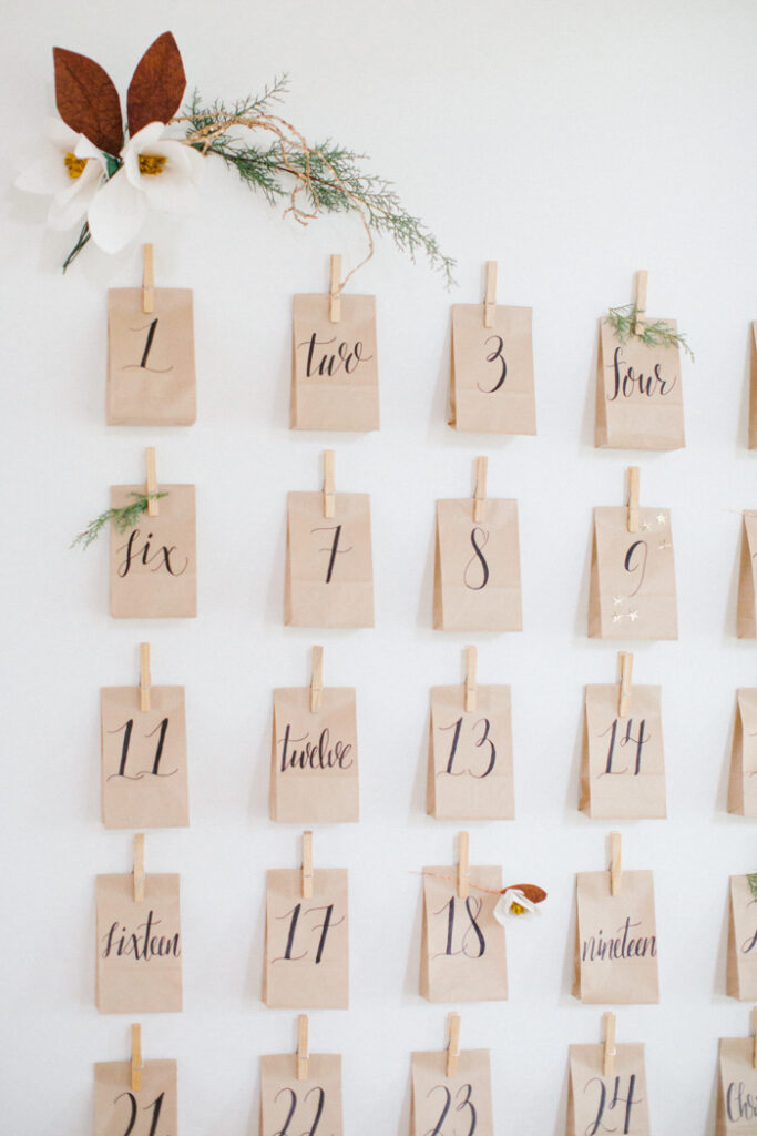 Paper bags pegged onto a wall with numbers written on the front.