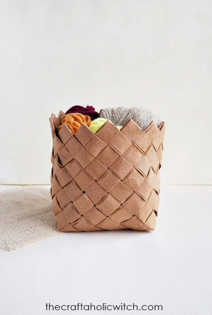 A woven paper basket filled with balls of yarn.