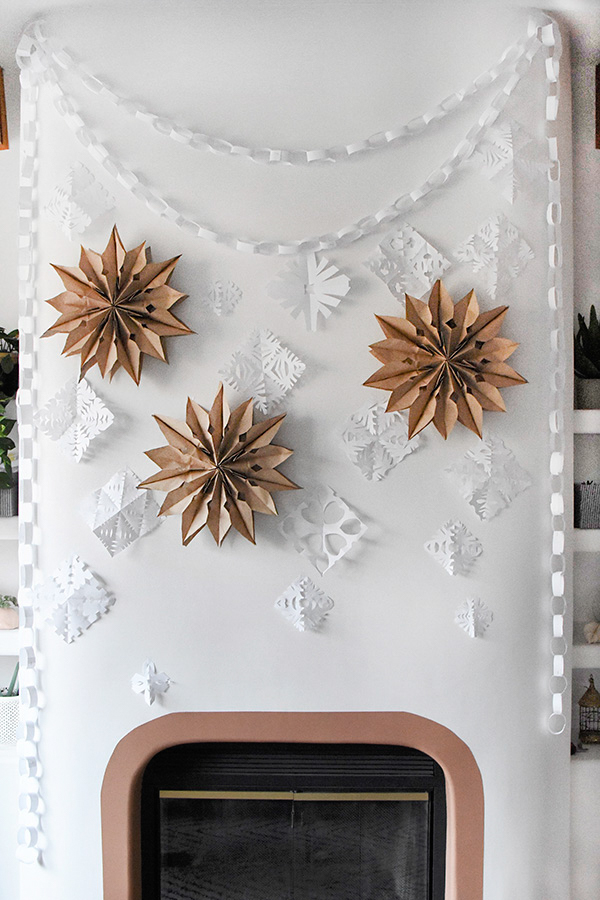 Paper bag snowflakes hanging on a wall.