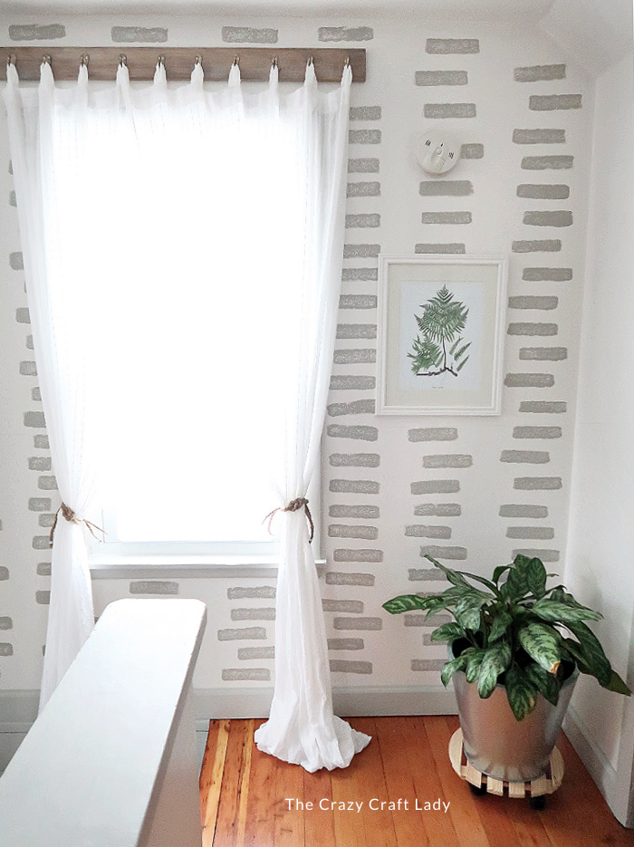 gray and white stencil feature wall with white curtains and rope curtain ties
