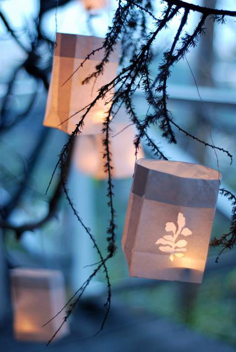 Paper bags with candles inside hung in a tree.