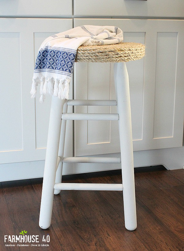 A white wooden bar stool with a rope seat.
