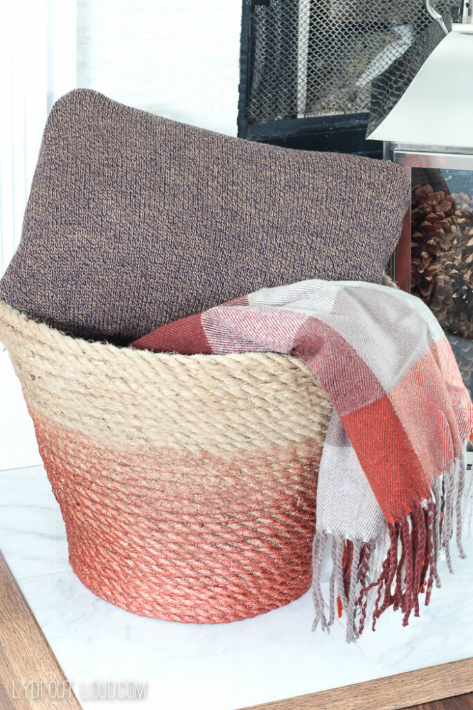 A rope basket filled with pillows and blankets.