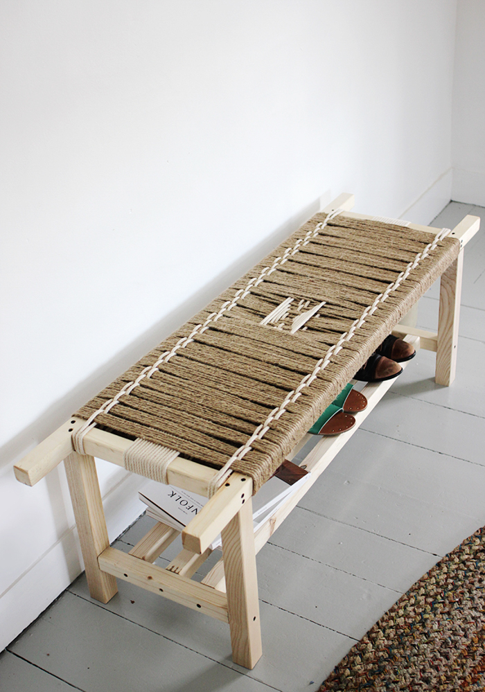 A wooden bench with a woven rope seat.